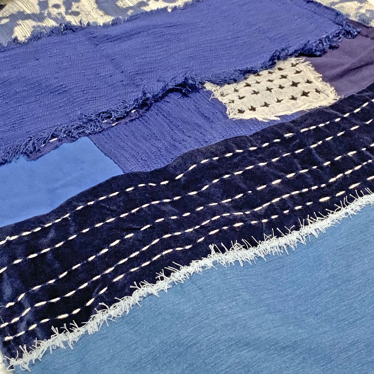 Detail of indigo dyed throw with white stitching across the indigo fabric