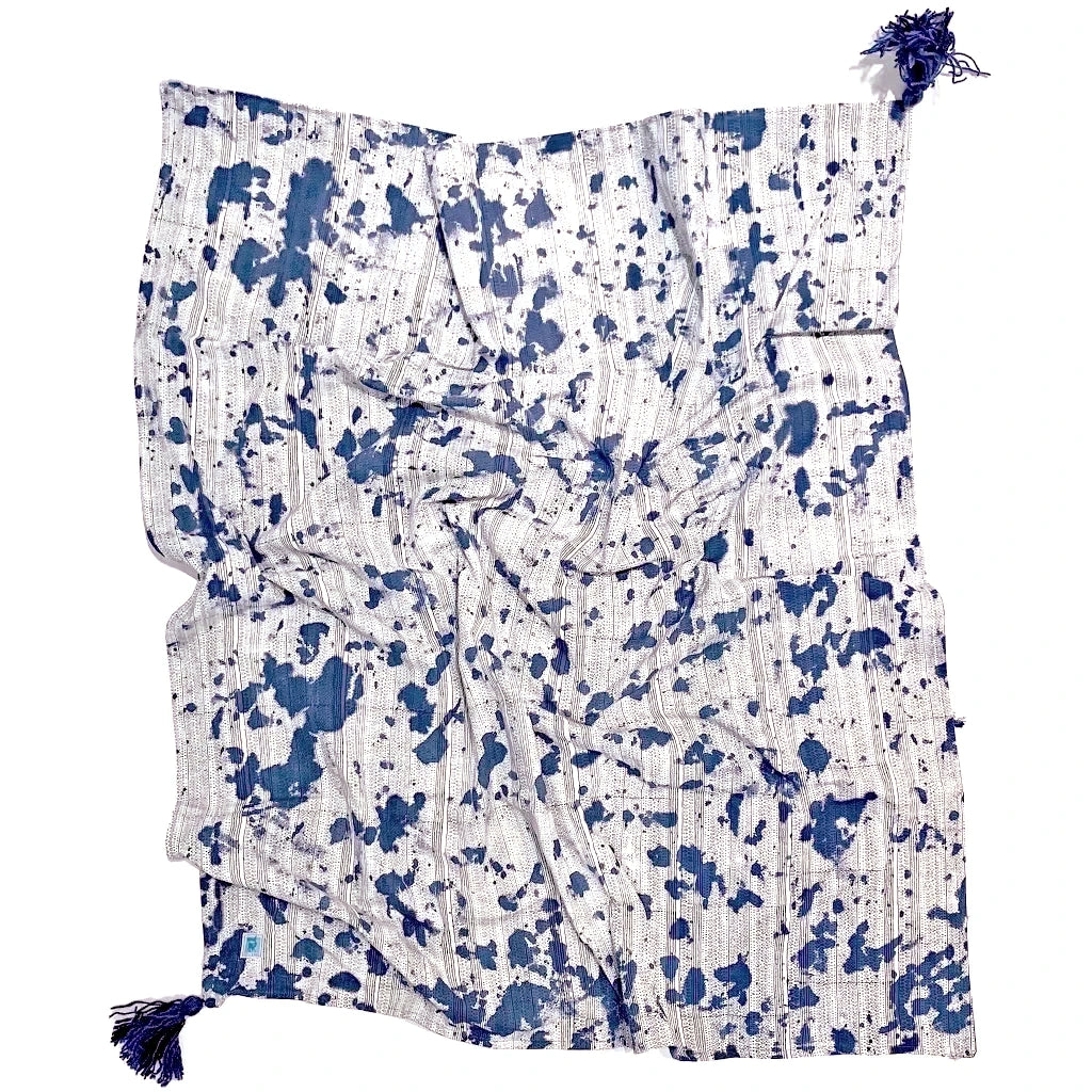 Reverse of indigo dyed throw. White with indigo splatters across the surface and blue tassels in the corners.