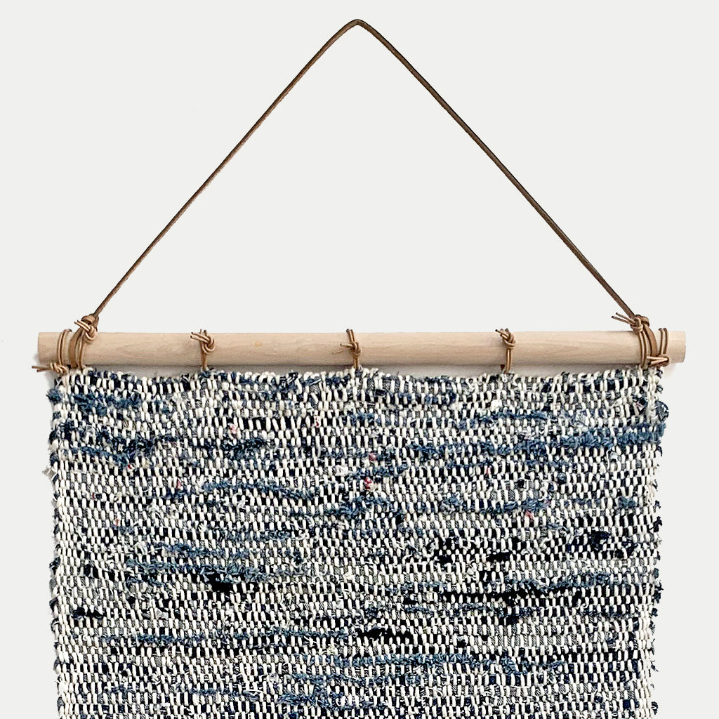 Hand Woven Upcycled Denim Tapestry on a wooden beam with frayed tasseled edges in white