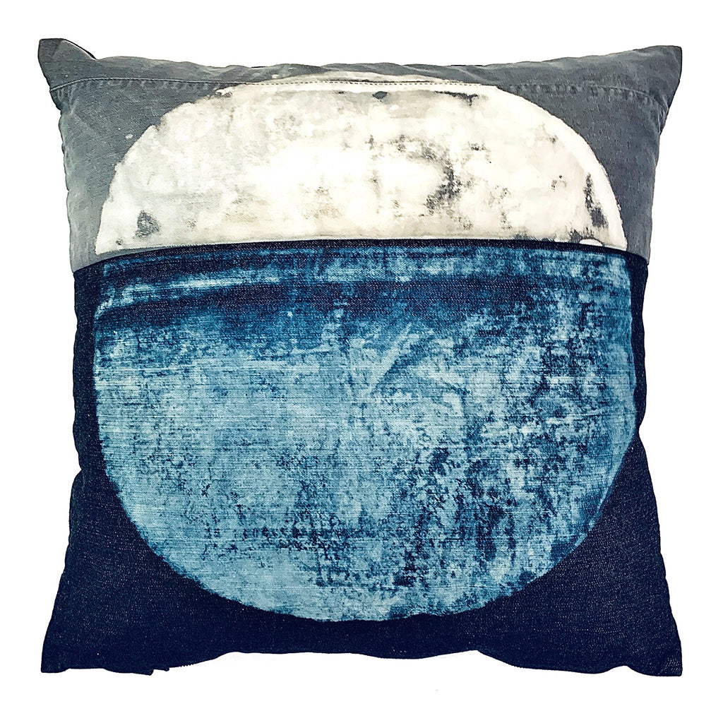 Decorative dark indigo and grey throw pillow with lighter indigo and white moon shape on the centre