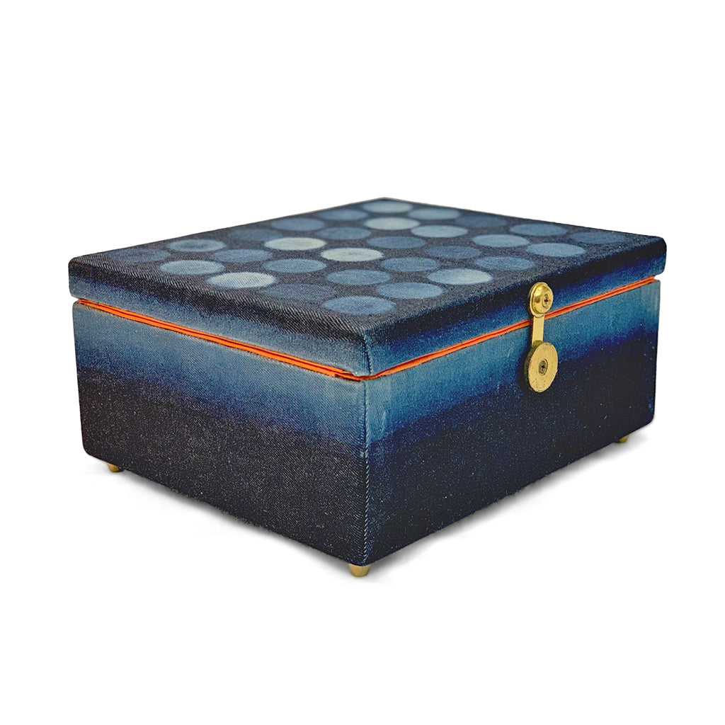 Rectangular indigo dyed box with gold clasp. top of the box features 6 x 6 rows of circles in varying shades of indigo, with bright orange interior of the box visible around the lid. base of the box is ombre dyed from darker to lighter indigo.