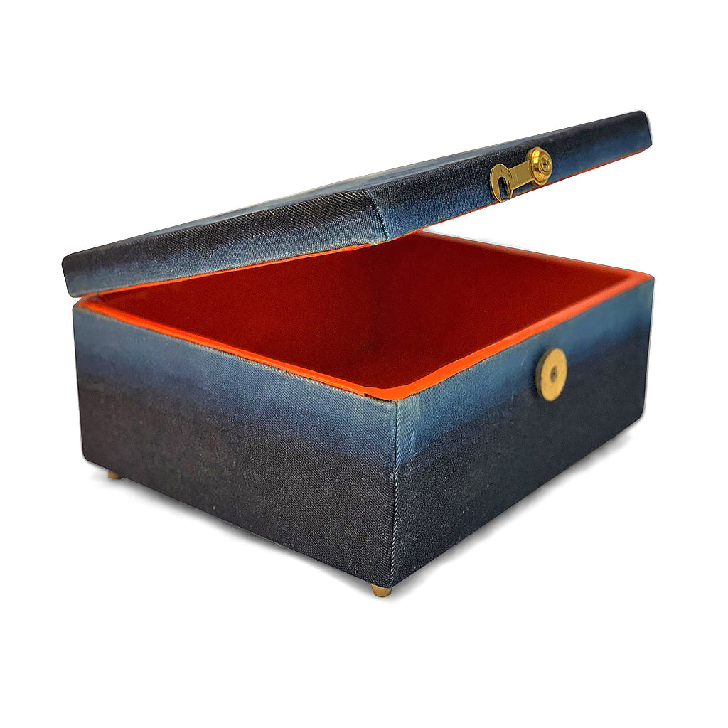 Orange inside of rectangular indigo dyed box with gold clasp. Rectangular indigo dyed box with gold clasp. top of the box features 6 x 6 rows of circles in varying shades of indigo, with bright orange interior of the box visible around the lid. base of the box is ombre dyed from darker to lighter indigo.