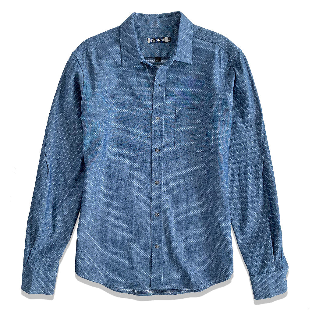 Mens chambray blue shirt. Fits slightly loose. Long sleeve, one pocket shirt with iconic gunmetal buttons. Twisted sleeve detail with double button detail at cuff.