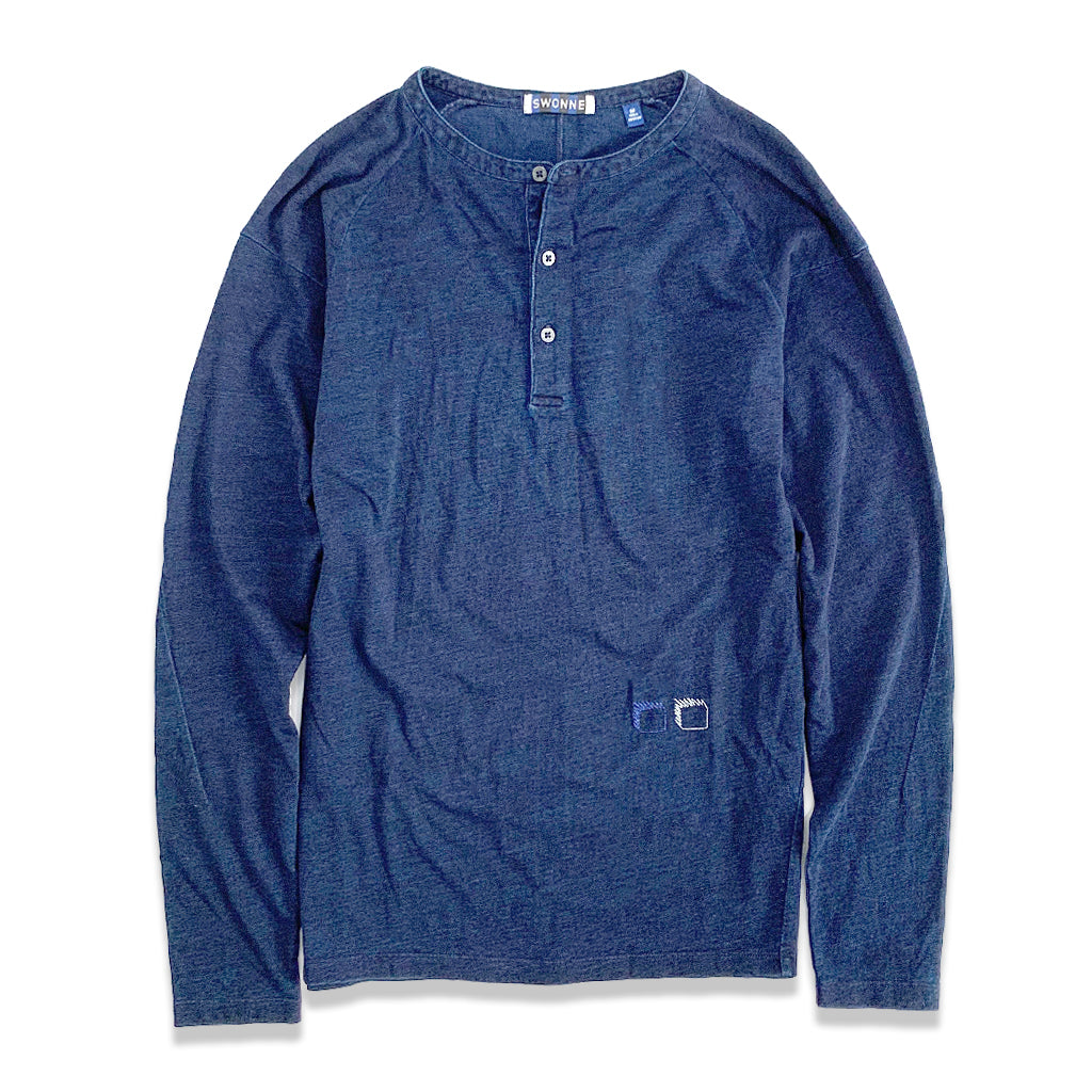 Swonne Indigo blue Henley Long Sleeve mens top with crew neck and three white buttons on the front. Two small embroidered square logos in white and blue on bottom left corner of the top