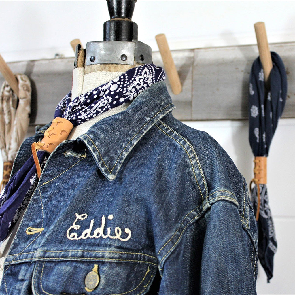 Blue 1950s vintage neckerchief bandana with hand tooled leather slides with deerskin lacing. Displayed on a mannequin with blue denim jacket.