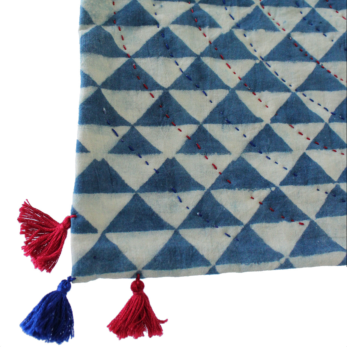 Corner of indigo dyed quilt with two red and one blue tassel