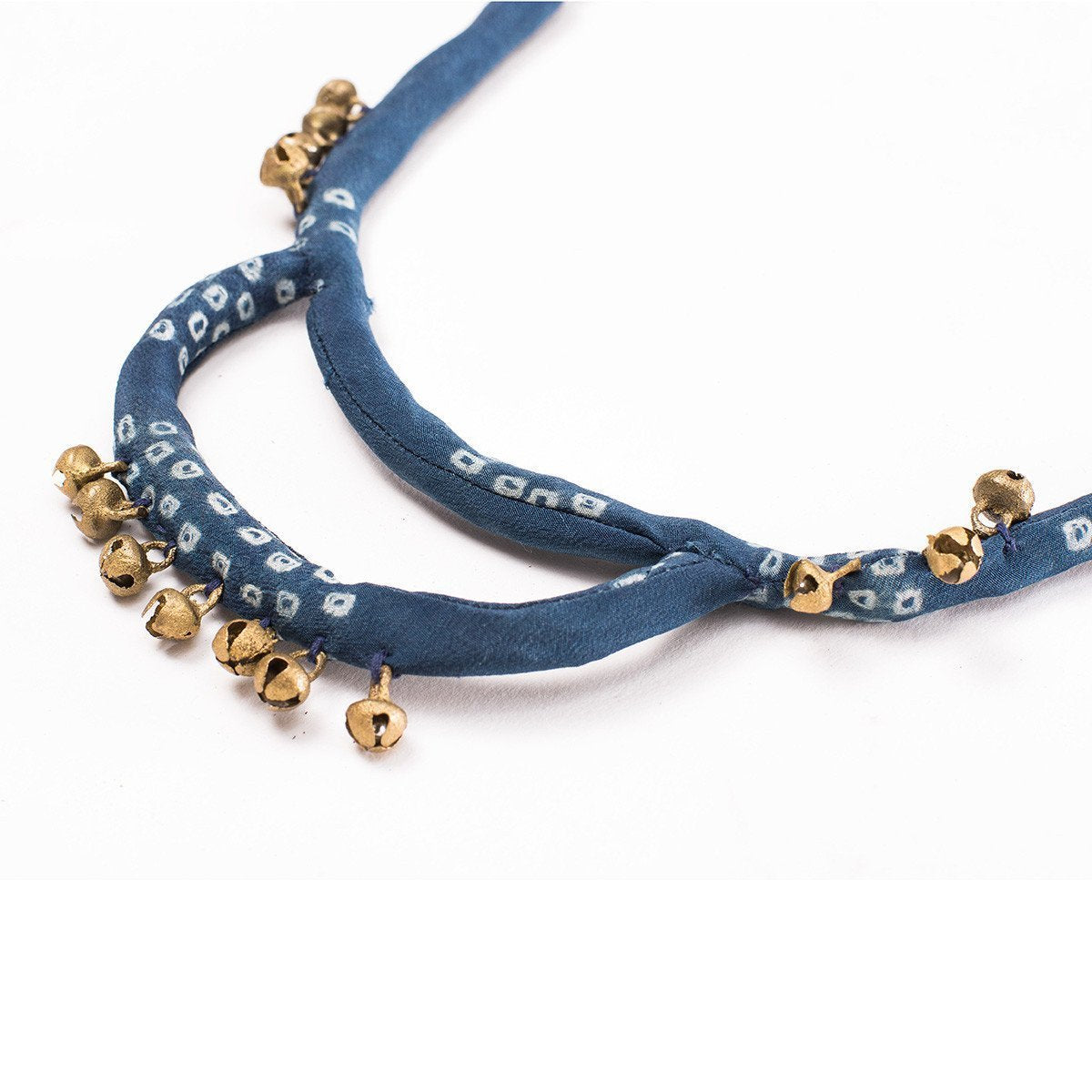 Engraved gold bell charms attached to an indigo silk dyed necklace
