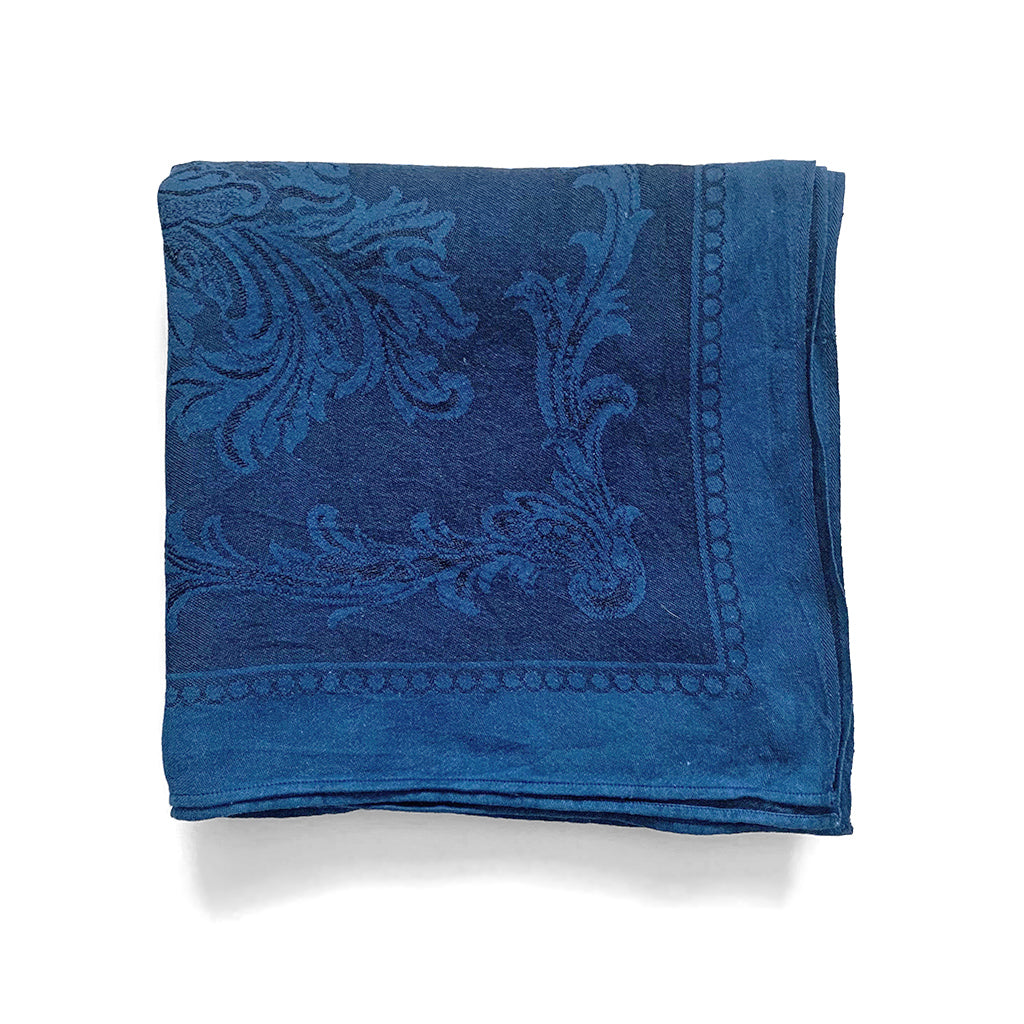 Indigo over dyed vintage Irish linen table cloth with floral jacquard pattern by Indiko shown folded