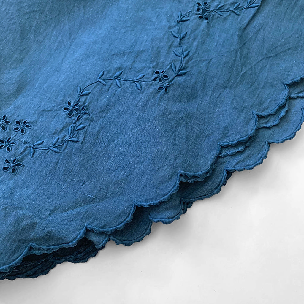 Detail of floral pattern and scalloped edging on indigo over dyed vintage round table cloth with embroidery by Indiko.