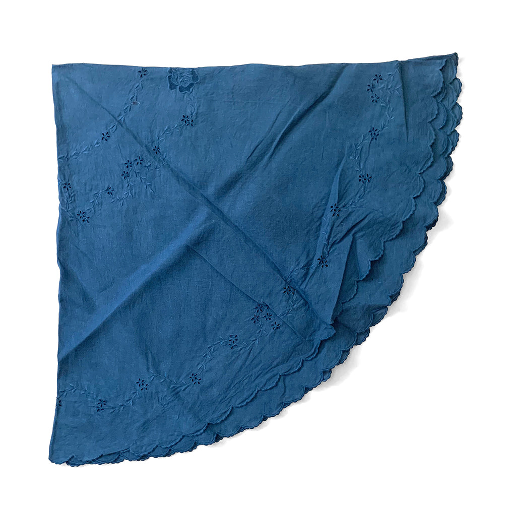 Indigo over dyed vintage round table cloth with embroidery and scalloped edging shown folded by Indiko
