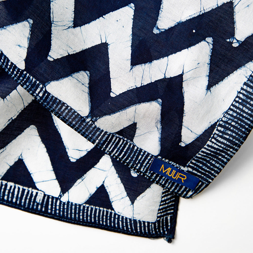 Detail of stitched edging and branded label on indigo and white chevron hand printed scarf by Muur