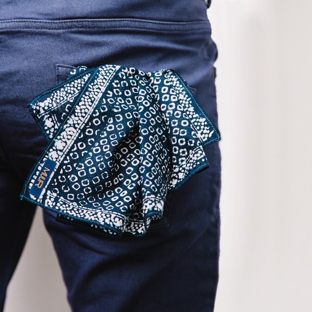 Hand painted indigo dyed bandana  by Muur in dot indigo and white print with darker stitched edging shown in man's back pocket