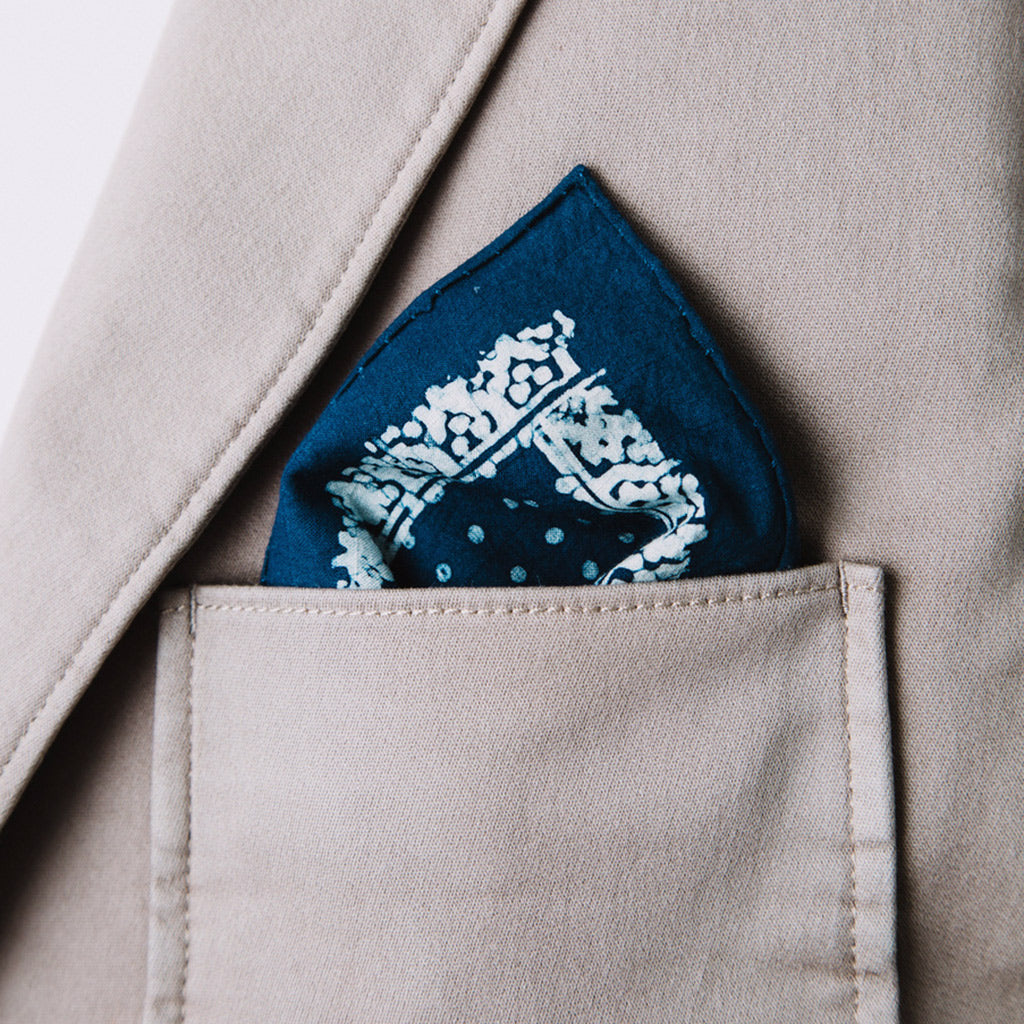 Hand painted pocket square dyed with indigo in a dot symmetrical pattern shown in jacket tan pocket by Muur
