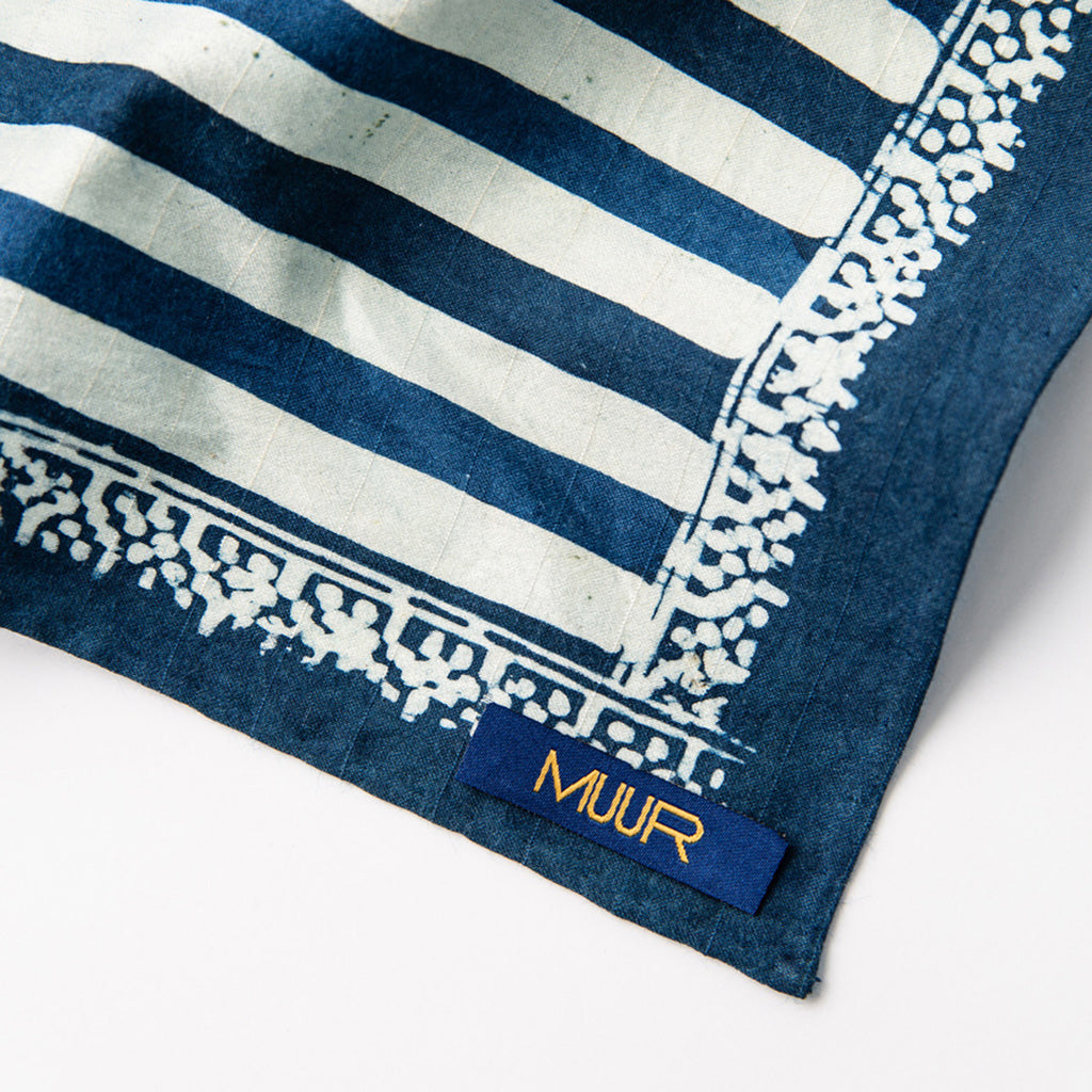 Muur logo label on the corner of Hand painted indigo dyed pocket square in stripes of indigo and white with solid indigo edge