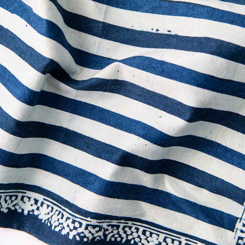 Detail of Hand painted indigo dyed pocket square in stripes of indigo and white with solid indigo edge