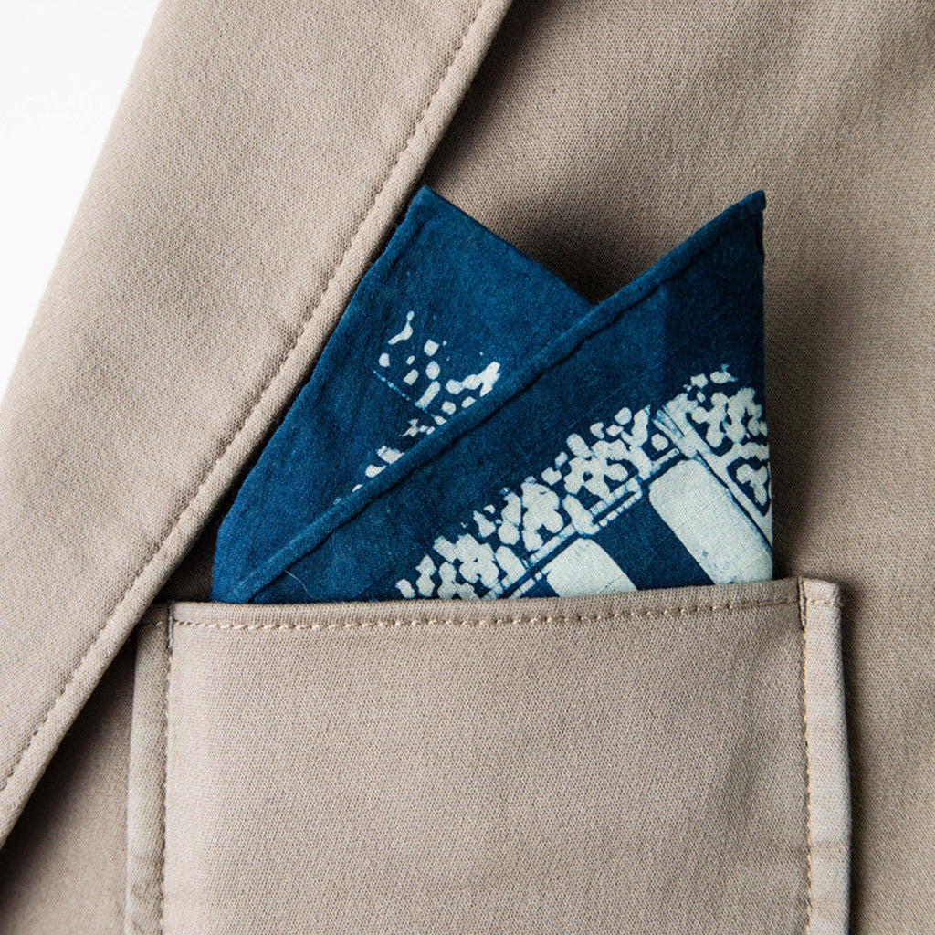 Hand painted indigo dyed pocket square in stripes of indigo and white with solid indigo edge shown in tan jacket breast pocket
