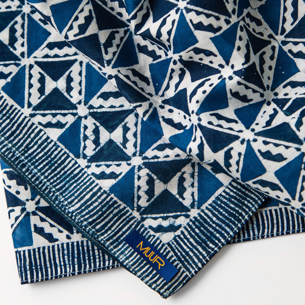 Detail of silk hand painted indigo dyed scarf in geometric print with striped edging by Muur