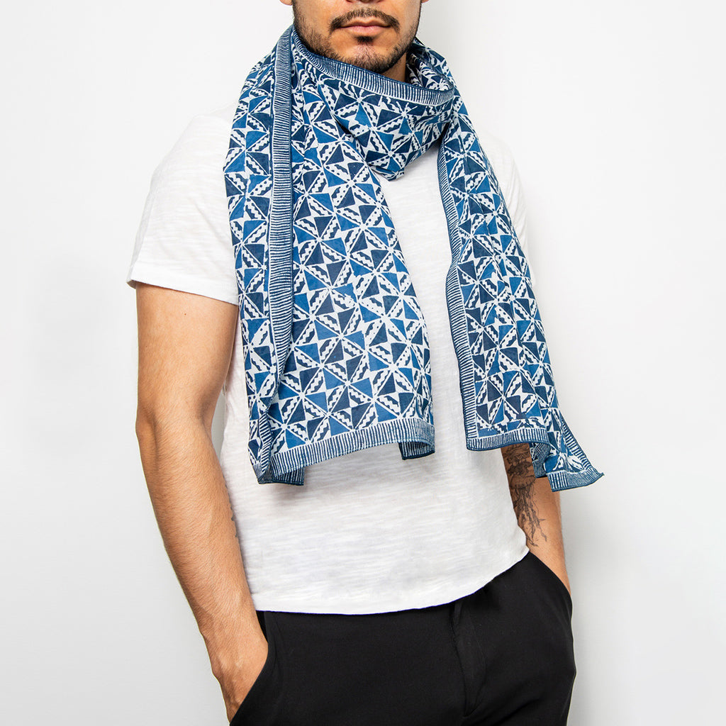 silk hand by muur painted indigo dyed scarf in geometric print with striped edging shown around a mans neck