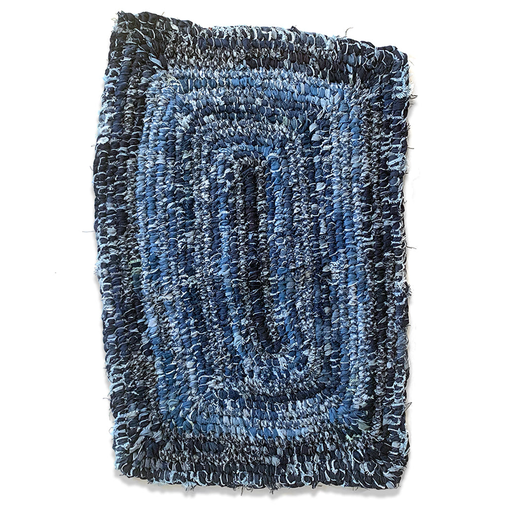 "Hand Woven Upcycled Denim ""Amish Knot"" Rug. Rectangular shaped with different rows of varied coloured indigo."