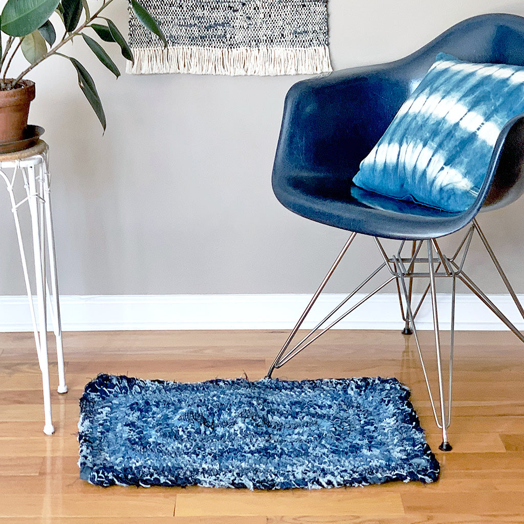 "Hand Woven Upcycled Denim ""Amish Knot"" Rug. Rectangular shaped with different rows of varied coloured indigo on a wooden floor with blue chair and plant on a plant stand."