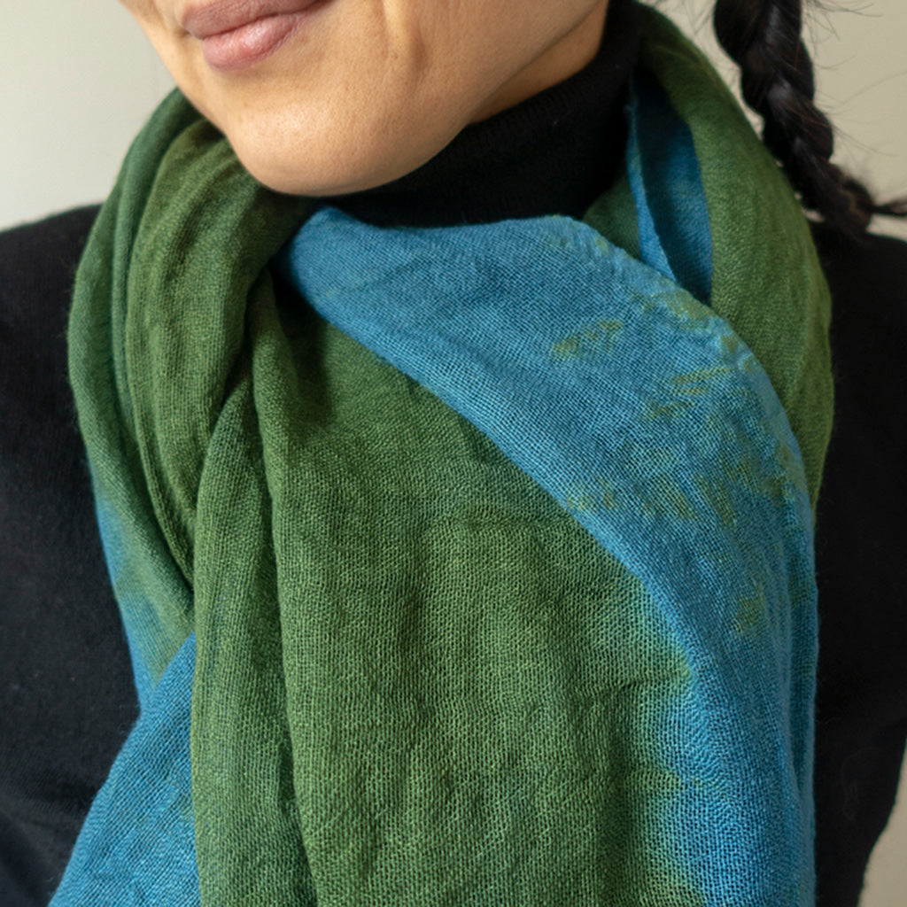 Indigo & Goldenrod Wool Scarf by Ricketts Indigo. 100% wool scarf dyed in green and blues with tasseled edges shown on a woman's neck/