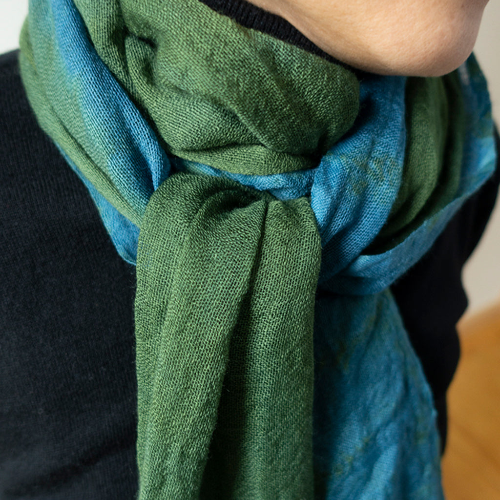 Indigo & Goldenrod Wool Scarf by Ricketts Indigo. 100% wool scarf dyed in green and blues with tasseled edges shown on a womans neck