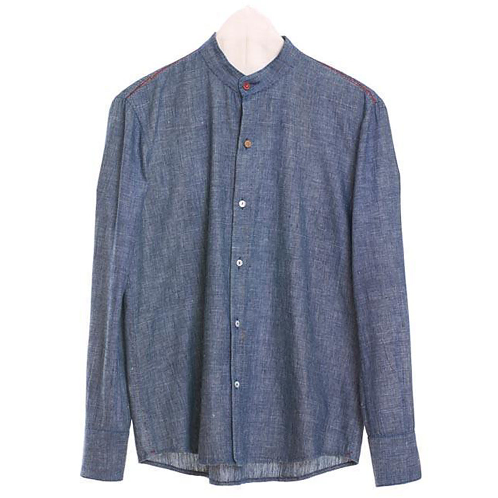 Blue chambray men's collarless shirt with red, brown and white buttons.