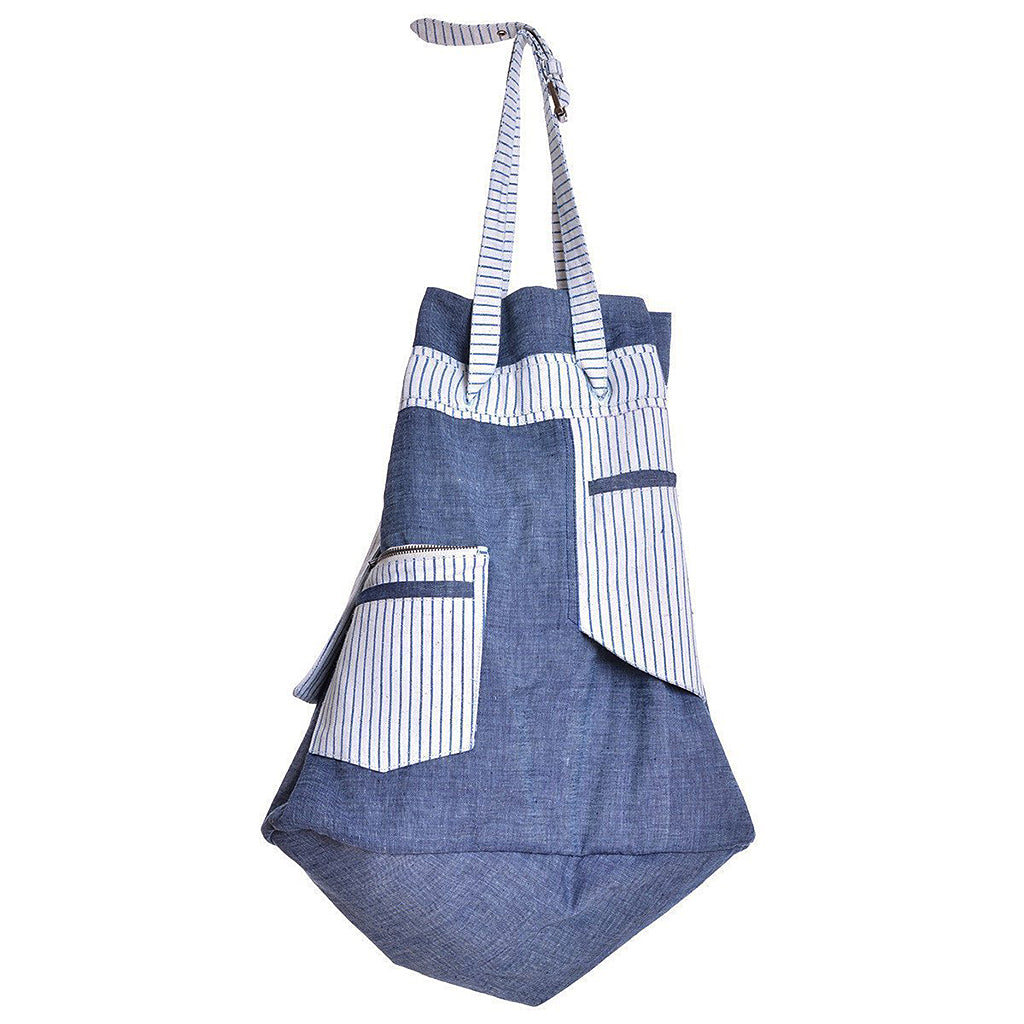 Side angle of indigo dyed chambray beach bag with striped straps and pocket.