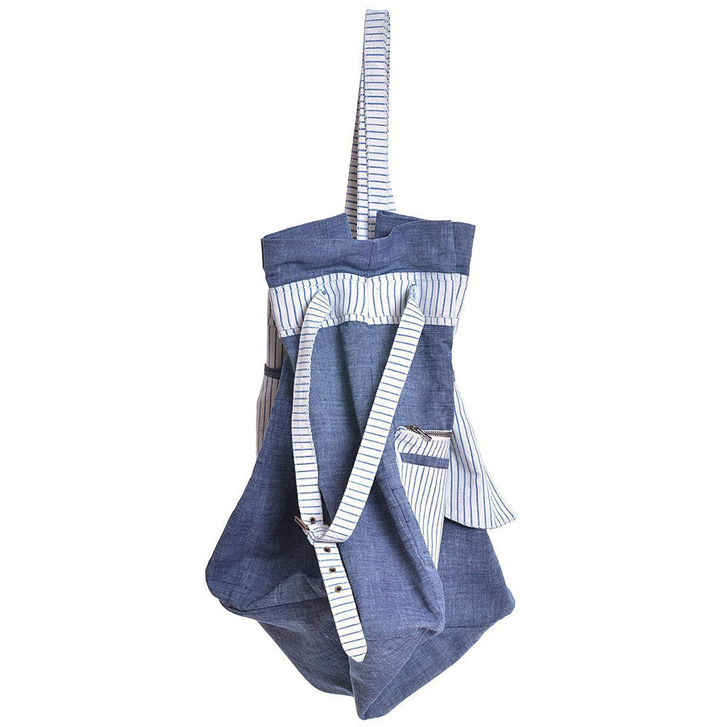 Side angle of indigo dyed chambray beach bag with striped straps