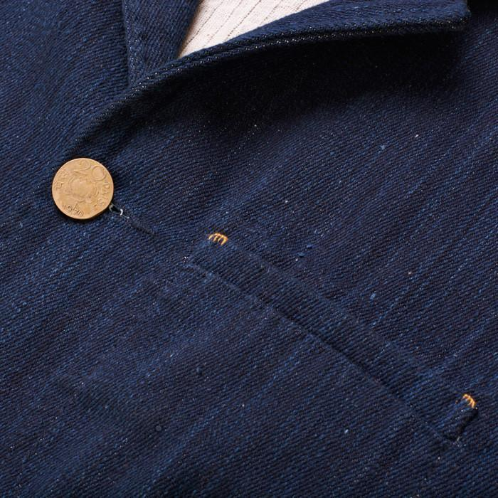 Copper button detail on men's indigo denim jacket