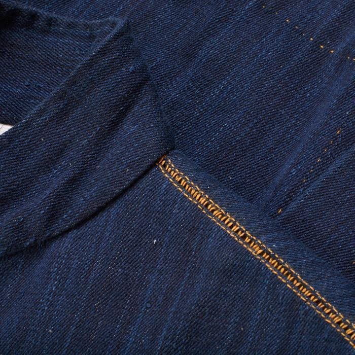 Detail of tan stitching on women's indigo denim jacket