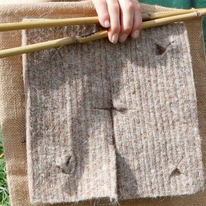 Close-up photo showing the wool mat, bamboo stakes and plant guard before installation