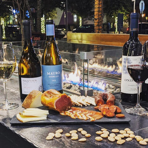 Local wine bar patio with fire. Enjoy a glass of red, white, bubbly or rose along with small bites including the pictured charcuterie.