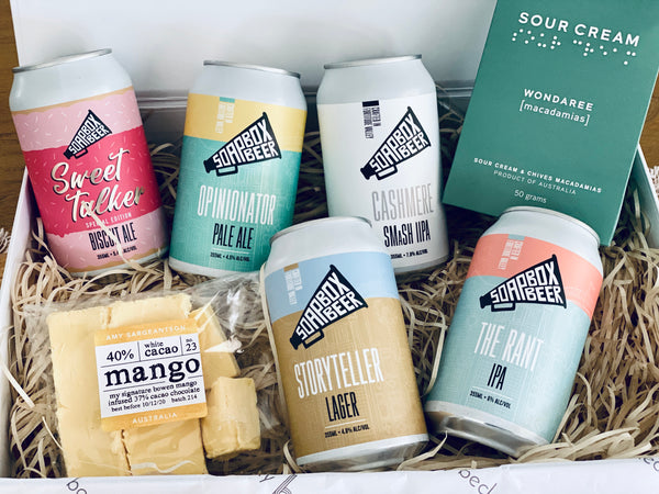 gift box including five queensland beer cans mango chocolate and wondaree macadamias