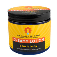 Beach Baby Creamy Lotion in 16 ounce cobalt blue jar and yellow label. Made with Aloe Vera, plumeria, coconut, and lemongrass