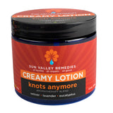 Knots Anymore Creamy Lotion in 16 ounce cobalt  jar, burgundy label. With organic Aloe Vera, vetiver, lavender, eucalyptus