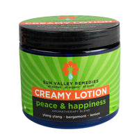 Peace & Happiness Creamy Lotion in 16 ounce cobalt jar, green label. Made with organic aloe vera, ylangylang, bergamot, lemon