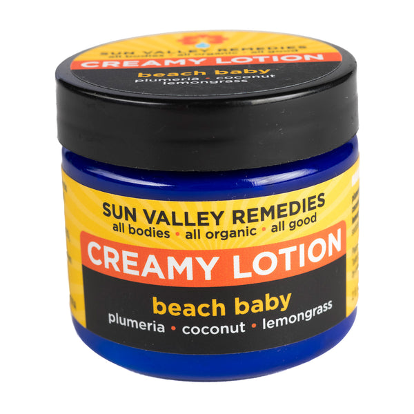 Beach Baby Creamy Lotion in 2 ounce cobalt blue jar and yellow label. With organic aloe vera, plumeria, coconut, lemongrass.