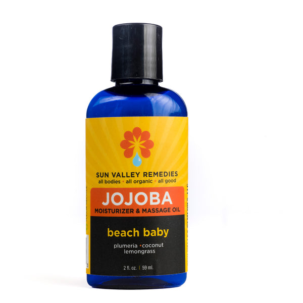 Beach Baby Jojoba oil in 2 ounce cobalt bottle and yellow label.  Made with organic Aloe Vera, plumeria, coconut, lemongrass