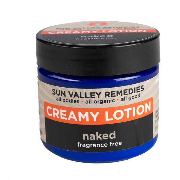 Naked Creamy Lotion in 2 ounce cobalt jar, beige label. made with organic Aloe Vera. Fragrance free, nourishing, luscious