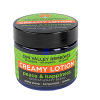 Peace & Happiness Creamy Lotion in 2 ounce cobalt jar, green label. Made with organic aloe vera, ylang ylang, bergamot, lemon