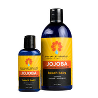 Beach Baby Jojoba oil in 2 sizes of cobalt bottles with yellow label.  Made with Aloe Vera, plumeria, coconut, and lemongrass