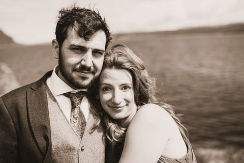 Dressed in formal wear, Andrew and Genna snuggle up on a seaside cliff