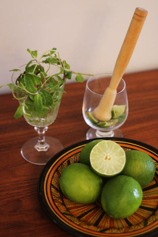 Lime wedges and mint being muddled in a glass with a cup of lime sprigs in the background and a bowl of limes in colourful plate in the foreground