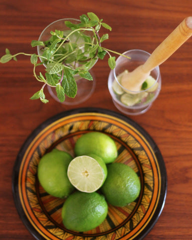 cup filled with mint sprigs, bowl of limes and limes and mint being muddled in a glass