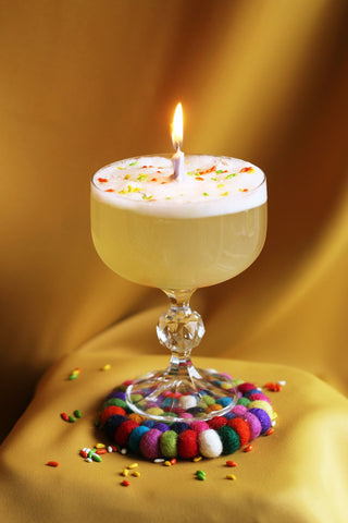 Cocktail in a coupe glass with a lit candle in the middle, egg white foam and candied fennel sprinkles