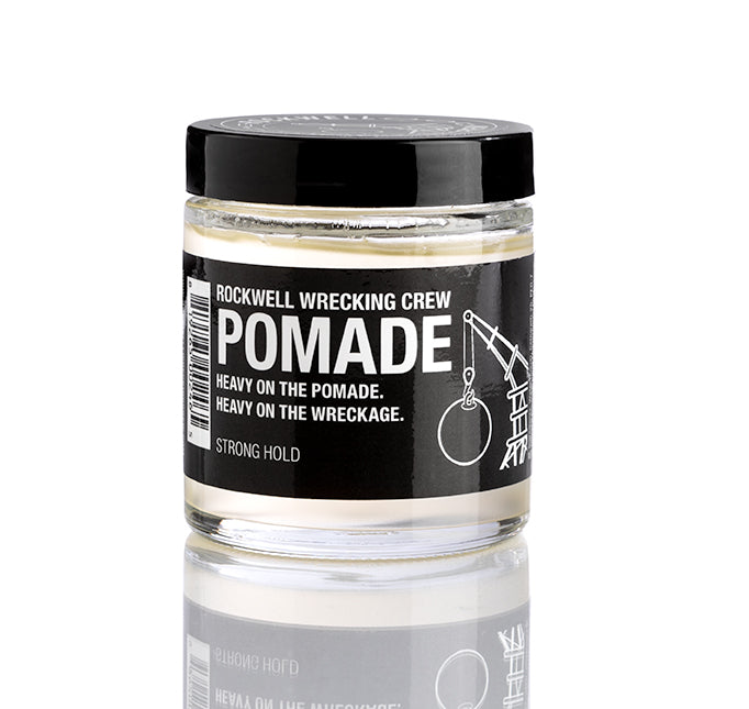 A photo of a glass jar of Rockwell Wrecking Crew Pomade on a white background. A small reflection of the glass jar can be seen.