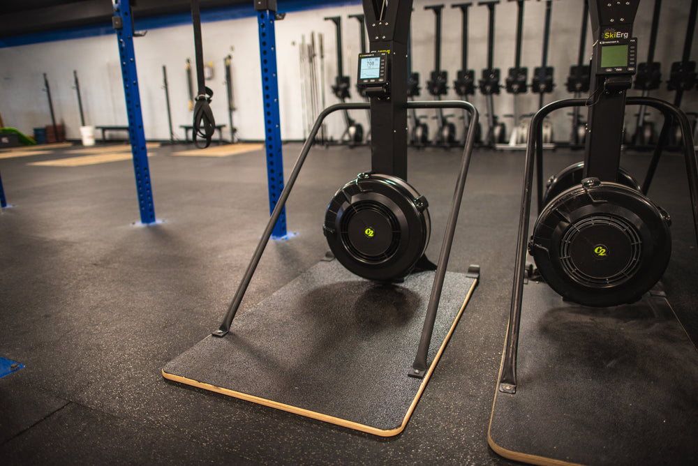 "Pictured are two Concept2 Ski Erg's, one with an Adaptive Base By Equip Products, and the other a standard size 24"" base in a gym setting on a black floor."
