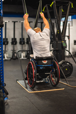 Pictured Kevin Ogar from the back using a Concept2 Ski Erg with the Equip Products Wider Base for Wheelchair users. In a gym setting on a black floor.