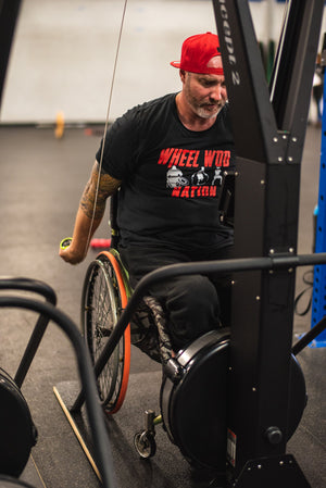 "Chris ""Stouty"" Stoutenberg in his wheelchair and pulling the handles downward on the Equip Products wider base for the Concept2 Ski Erg, in a gym setting on a black floor."